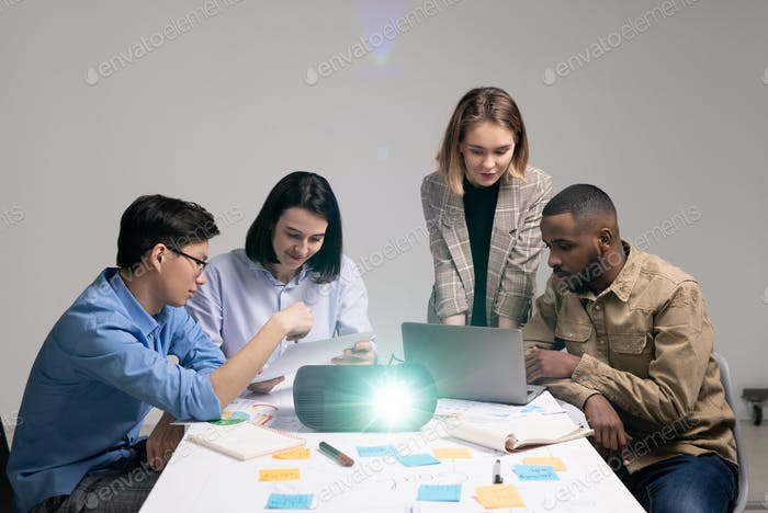 Multi-ethnic group of young contemporary analysts or financiers brainstorming