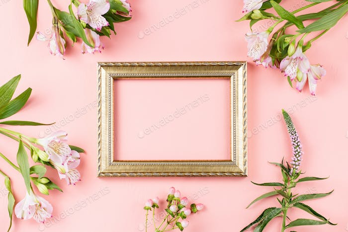 Golden photo frame with flowers on pastel pink background, copy space