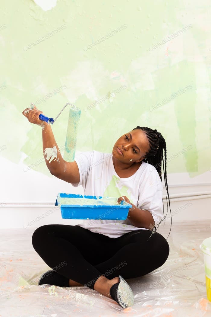 Afro american woman painting an apartment. Renovation, repair and redecoration concept