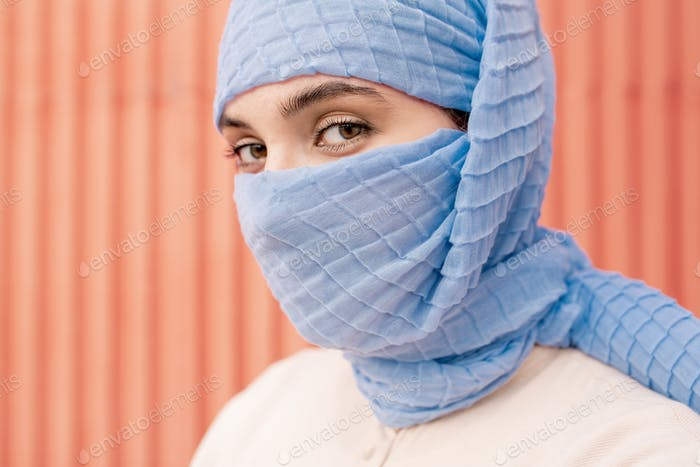 Young beautiful Arabian female with her face hidden behind blue hijab