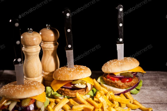Fast food of tasty delicious burgers on wooden background next t