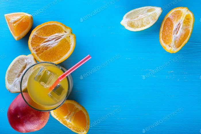 Fresh raw fruits and glass of juice on blue background