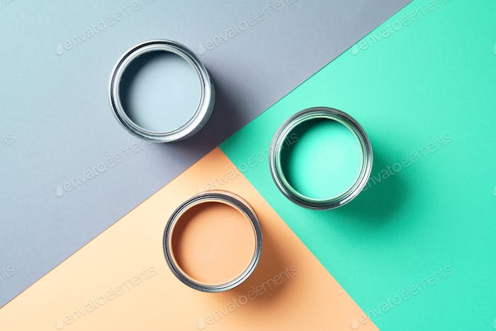 Open cans of paint on bright multicolored background. Top view. Copy space. Trendy green color
