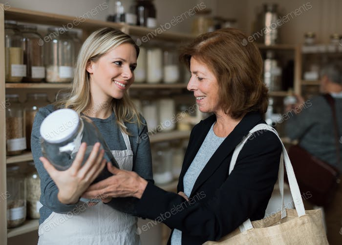 A female shop assistant serving a senior customer in a zero-waste shop.