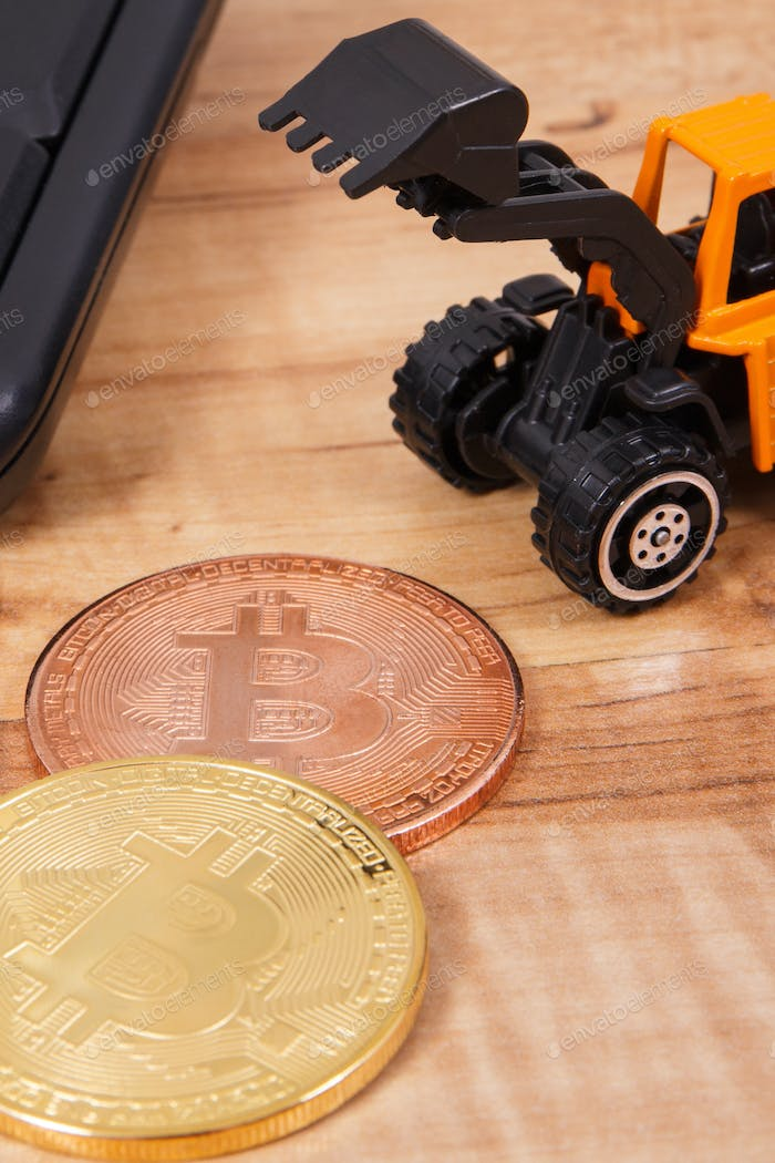 Bitcoins, miniature excavator and computer keyboard