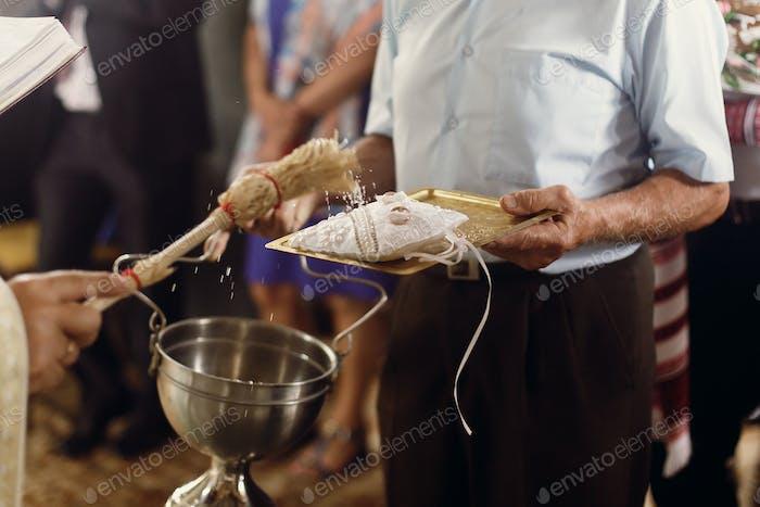 Orthodox christian priest showering golden wedding rings