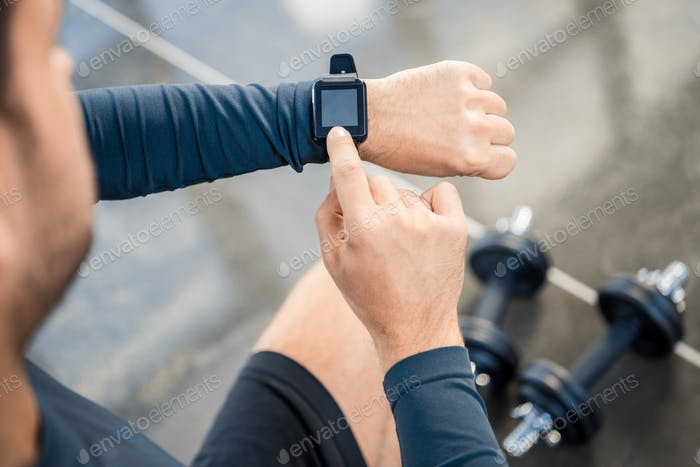 young man using smartwatch at gym