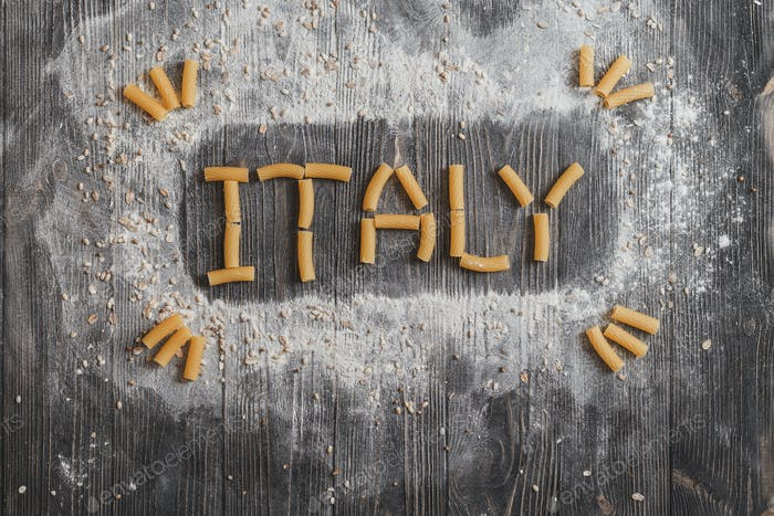 Lettering ITALY pasta on black rustic wooden background. Top view