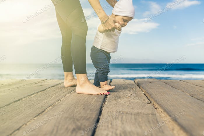Baby boy walking on the beach in beautiful summer day