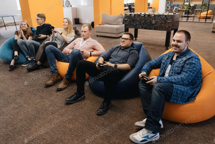 An IT team Play video games on the console while relaxing after work