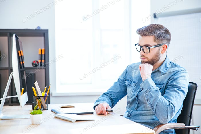 Thoughtful designer using graphic tablet and computer
