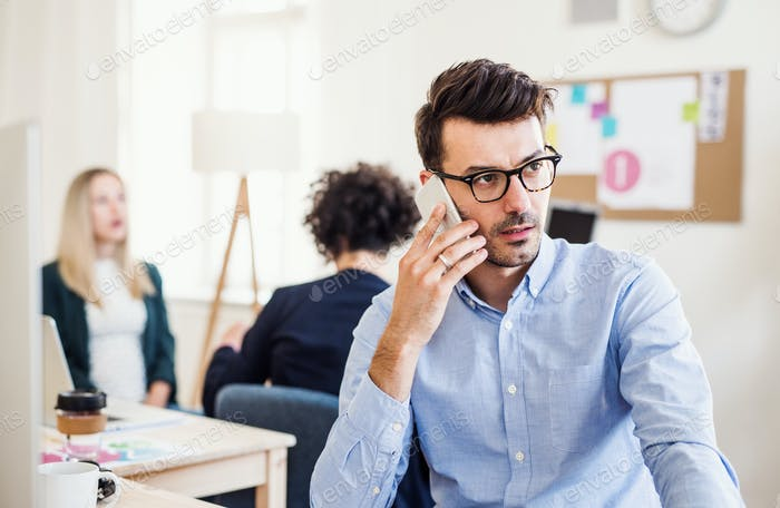 Young businessman with smartphone working in a modern office.