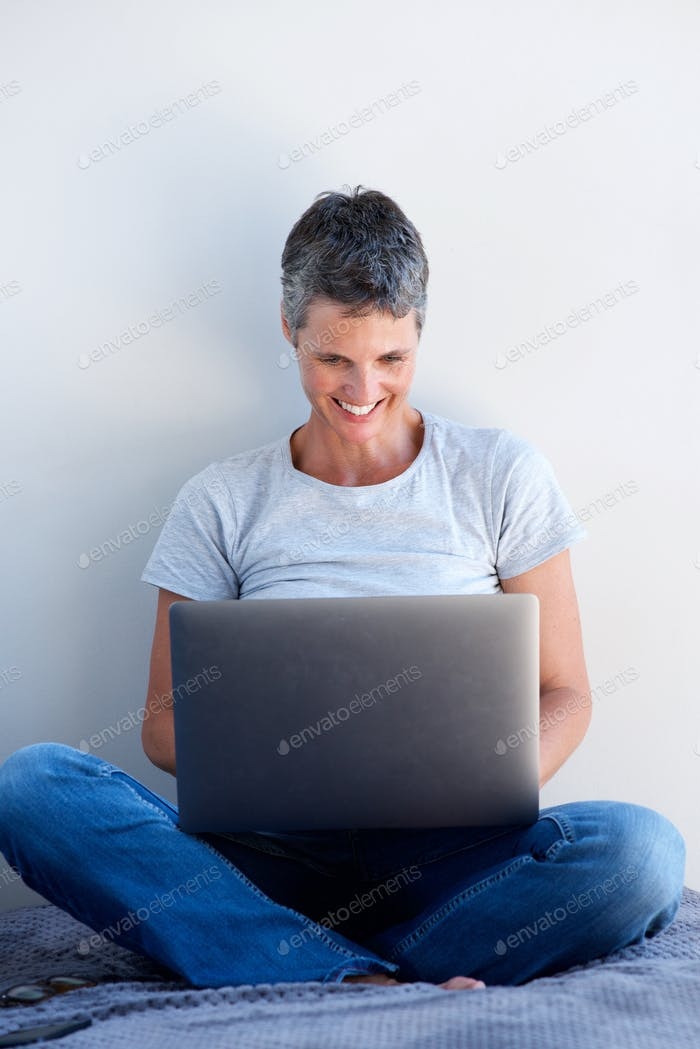 attractive older woman smiling and using laptop