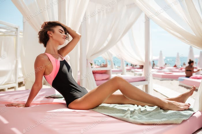 Girl in trendy swimsuit sitting in beach tent and dreamily closing eyes while tidying her hair