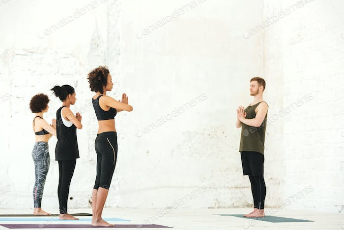 Group of multiethnic people standing in yoga studio