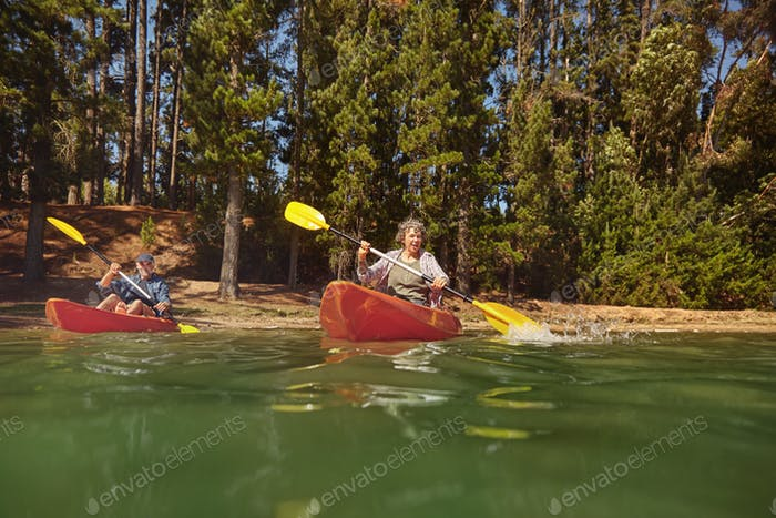 Mature couple canoeing on a lake during a camping trip