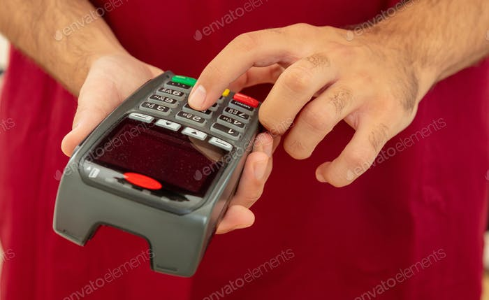 Man typing on a POS terminal, payment with credit card. Banking, shopping concept.