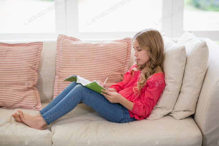 Girl sitting on sofa and doing homework in living room