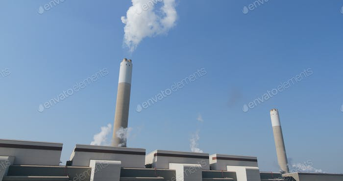 Smoke from chimney in factory over blue sky
