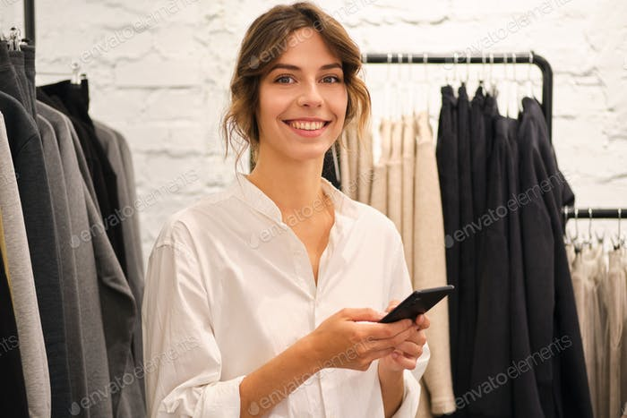 Young beautiful casual woman happily looking in camera using cellphone in modern showroom