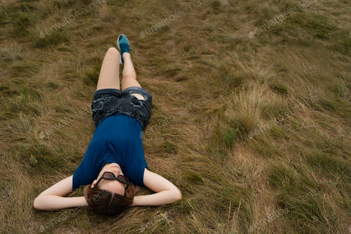 Woman with sunglasses and shorts lying in the grass