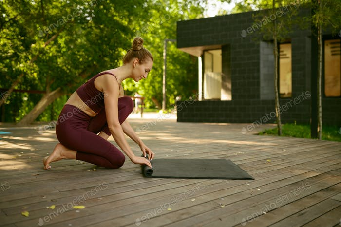 Slim woman twists mat after yoga training in park