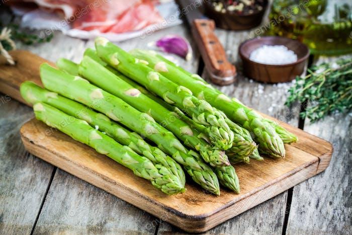 Fresh organic asparagus on a cutting board with Parma ham