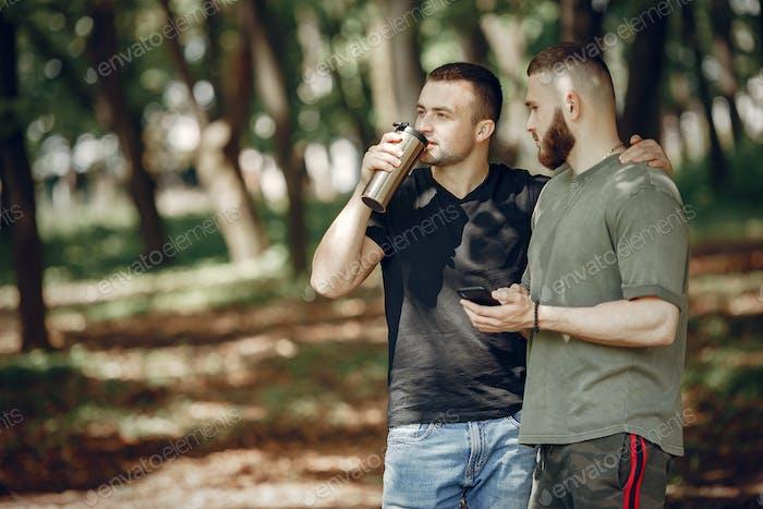 Zwei Freunde haben eine Pause in einem Sommerwald