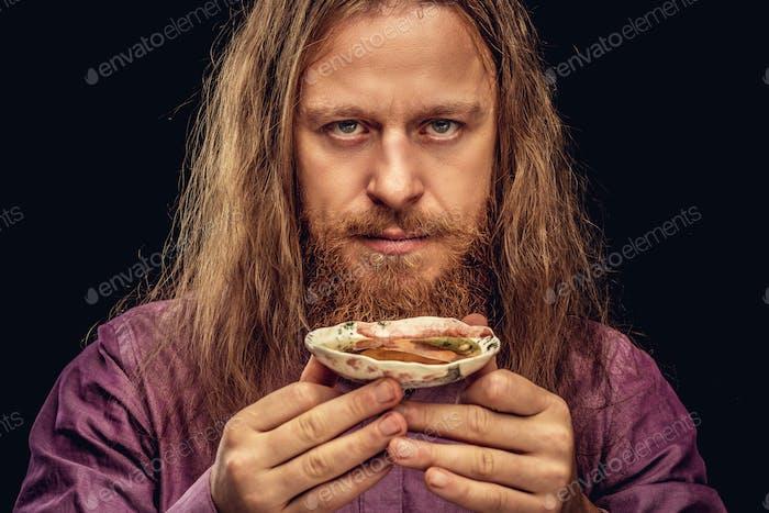 Счастливый рыжий хипстер мужчина с держит небольшую блюдце с чаем, глядя на камеру