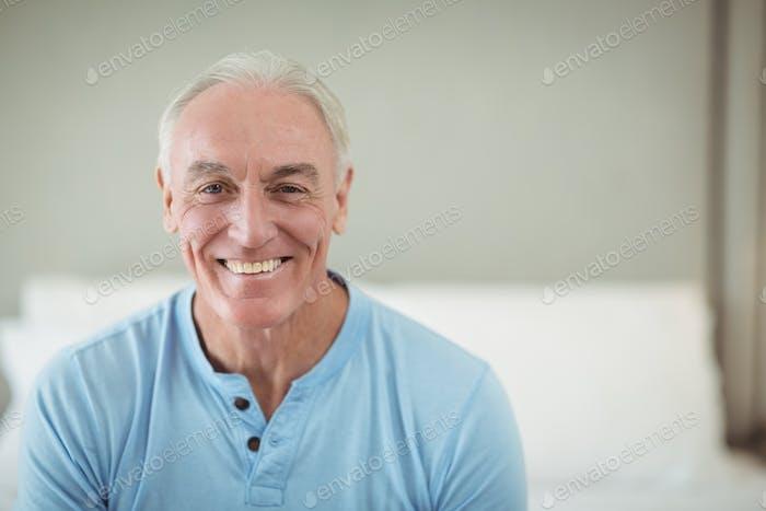 Happy senior man sitting on bed