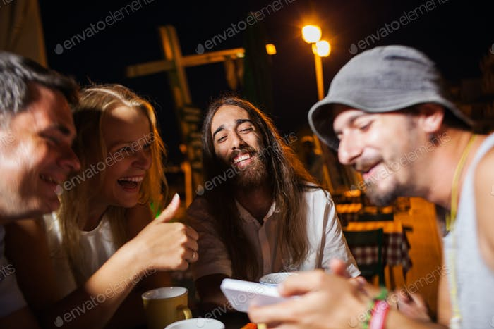 Happy friends watching photos on the cell