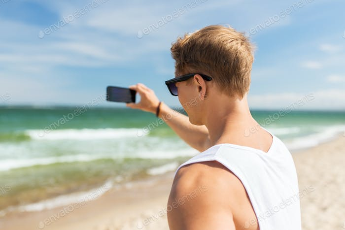 man with smartphone photographing on summer beach