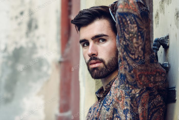 Close-up portrait of young bearded man, model of fashion, in urb