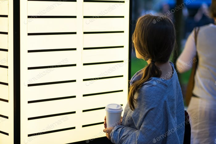 beautiful woman looking with interest on blank billboard deciding where to go