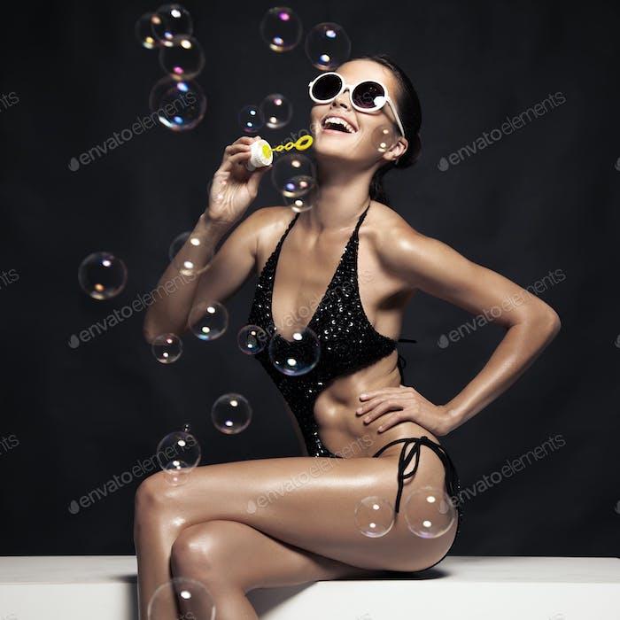 Schöne tan weibliche Modell posiert in Bikini und Blow Bubbles