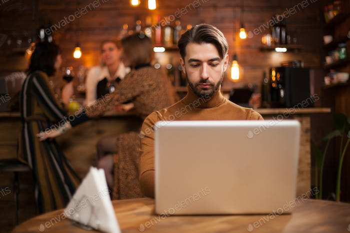 Handsome businessman working on his laptop in a vintage coffee shop