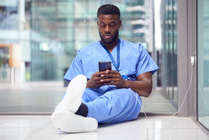 Male Medical Worker In Hospital Addicted To Using Mobile Phone At Work