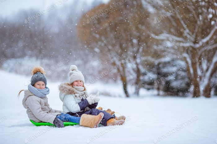 Adorable little happy girls sledding in winter snowy day