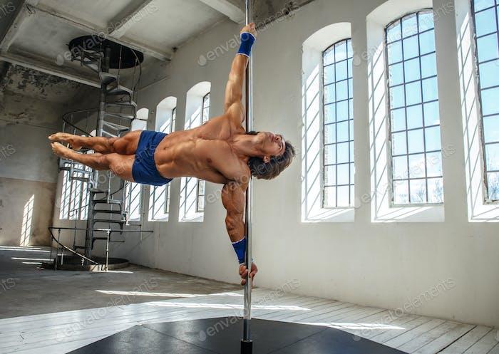 Shirtless man pole dancing.