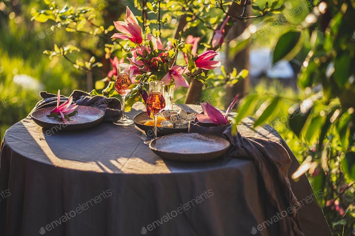 Table decorated with magnolia flowers under magnolia tree.