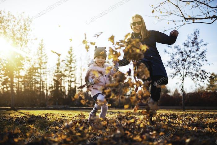Mom and daughter having fun at the park. Fall season