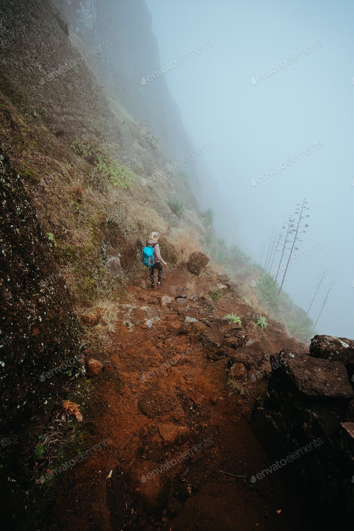 Hiker women with backpack walking down the steep slope of the rock in the foggy mountains