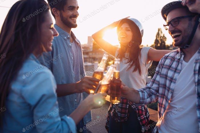 Junge Freunde hängen mit Drinks auf dem Dach