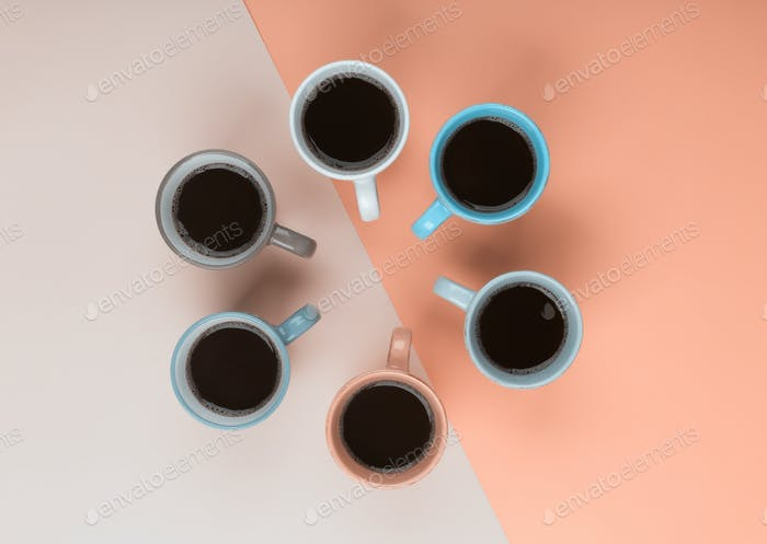 Coffee in the different cups on the coral background. Flatlay, cheerful day concept