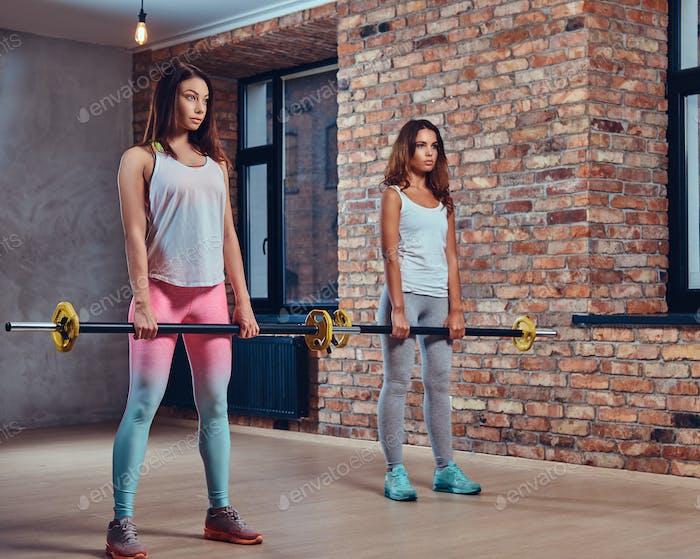 Женщины в спортивной одежде держат штанги.