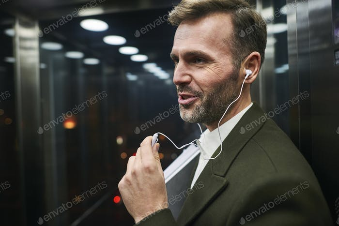 Side view of happy businessman listening to music in elevator