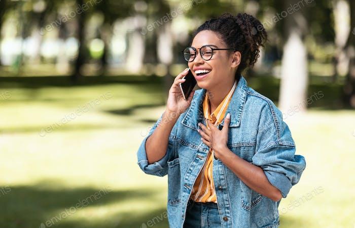 Happy African American Girl Talking On Cellphone Walking In Park