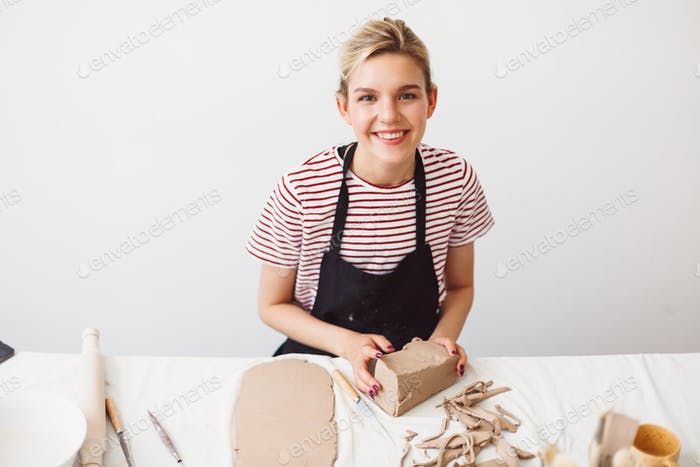 Girl in black apron and striped T-shirt sitting with piece of clay happily looking in camera