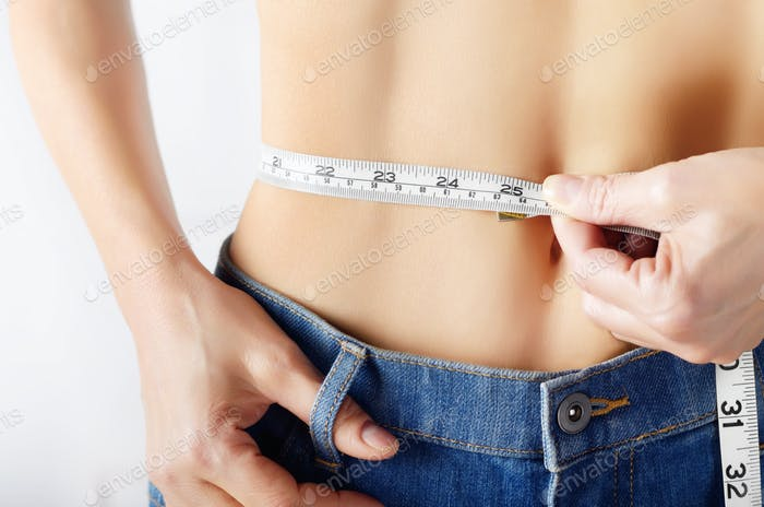 Caucasian female model in blue jeans with tape measure showing her flat stomach