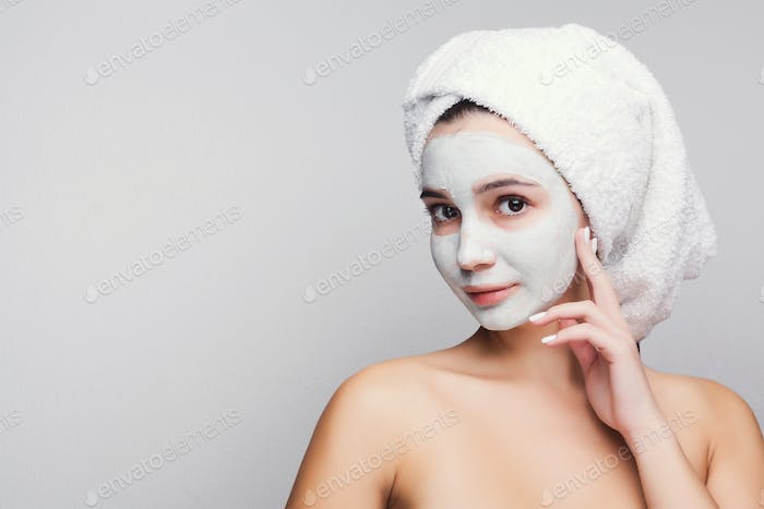 Beautiful girl with applied clay mask at white background